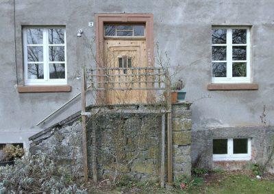 antike Haustür mit Sandsteinrahmung