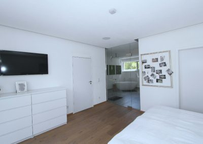 Schlafzimmer 1 im Erdgeschoss mit Verglasung zum Bad